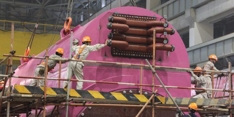Китайские специалисты монтируют турбину в машинном зале